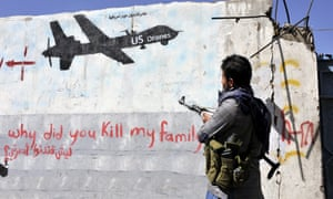 A gunman loyal to the Shiite Houthi movement looks at graffiti protesting US drone operations a day after a US drone killed suspected al-Qaeda in the Arabian Penninsula (AQAP) militants, Sana'a, Yemen, October 2014.