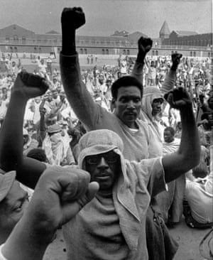 Inmates at Attica state prison in New York raise their fists in solidarity during a negotiation session with the state prisons commissioner, Russell Oswald, on 10 September 1971.