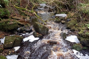 bubbles and white foam spinning between boulders in the Hareshaw Burn