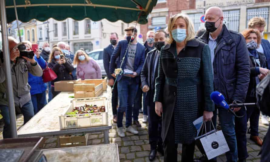Marine Le Pen visiting market all in masks.