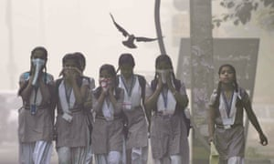 Children cover their face amid heavy smog in the early morning at Mayur Vihar, New Delhi, India
