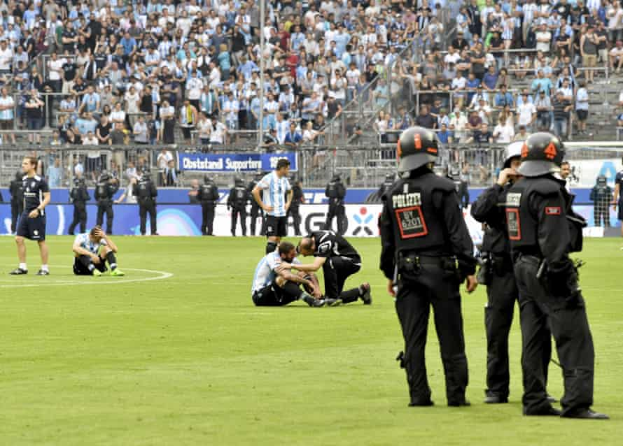 1860 Munich players sit on the pitch after losing the German Bundesliga 2nd division relegation match against Jahn Regensburg in the Allianz Arena