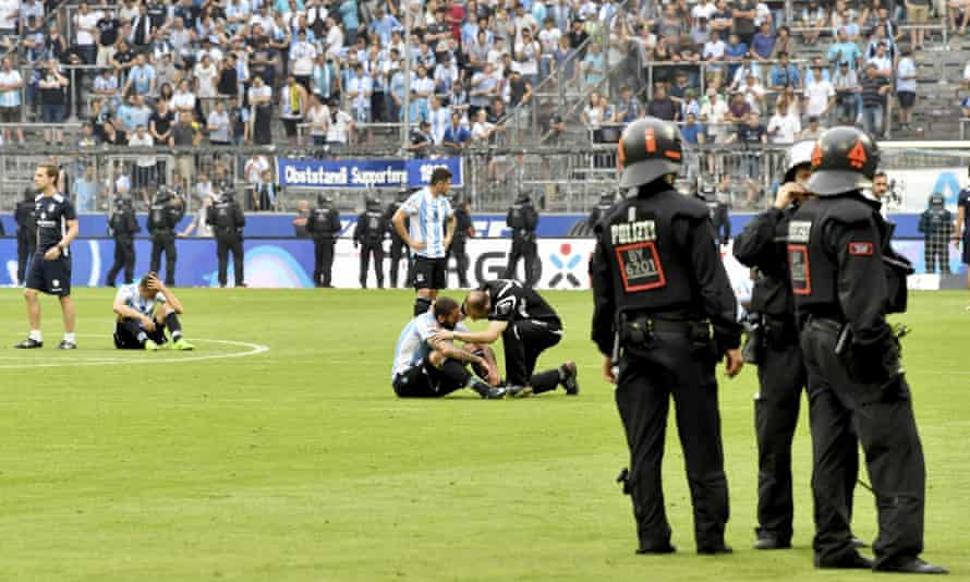 1860 Munich players sit on the pitch after their relegation play-off defeat against Jahn Regensburg, at the Allianz Arena.