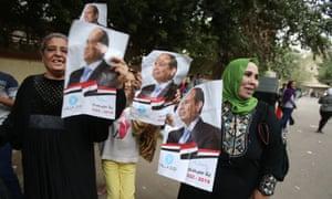 Egyptian women hold a poster of Egyptian president Abdel Fatah al-Sisi during voting last week