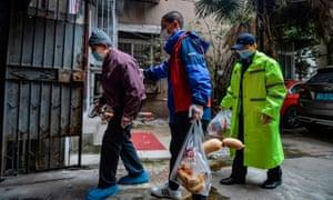 Community volunteers escort an elderly resident home in Wuhan earlier this month.
