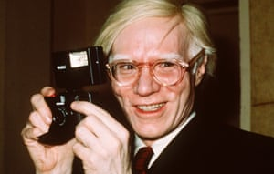 Pop artist Andy Warhol holds a camera in New York in 1976