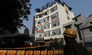 A firefighter outside the Delhi hotel where a fire killed at least 17 people.