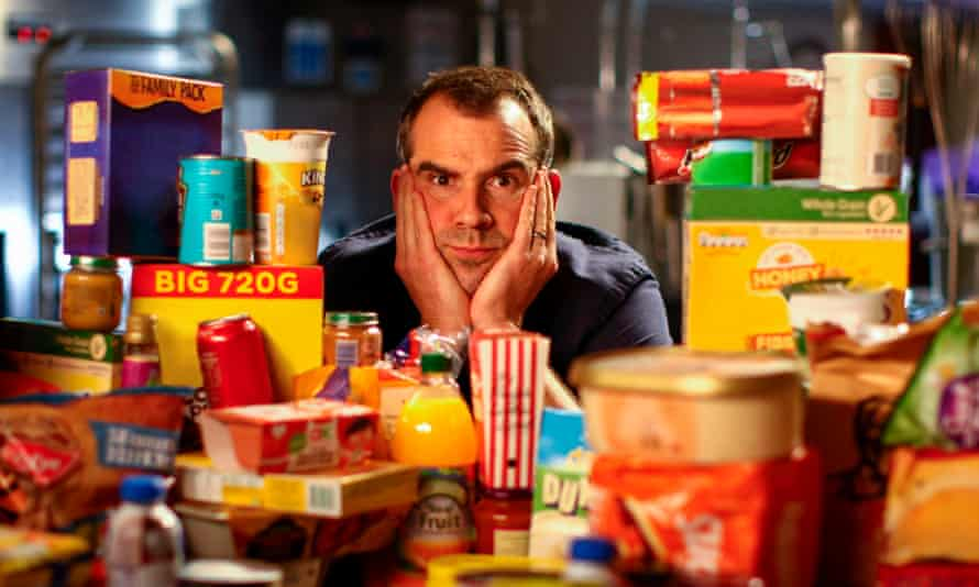 Dr Chris van Tulleken surrounded by an array of ultra-processed foods