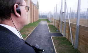 A security guard surveys the boundaries of Yarl's Wood immigration removal centre, near Bedford.
