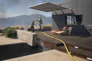 Firefighters protect a Pacific Palisades area home in Los Angeles from the flames of a wildfire.