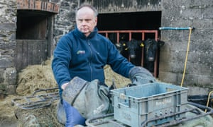 Wyn Evans poses on a tractor in his farm in West Wales.