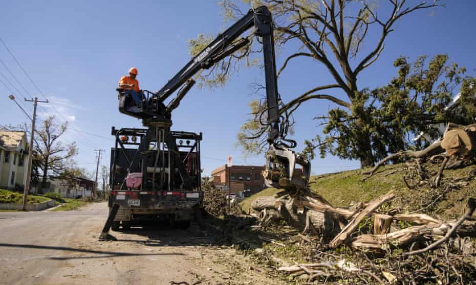 A crew removes a tree downed in the derecho wind storm in a residential neighborhood of Cedar Rapids, Iowa.