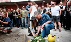 People leave flowers and candles during a memorial service for Eric Torell in Sweden