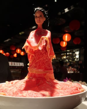 A Barbie doll covered in strips of raw meat