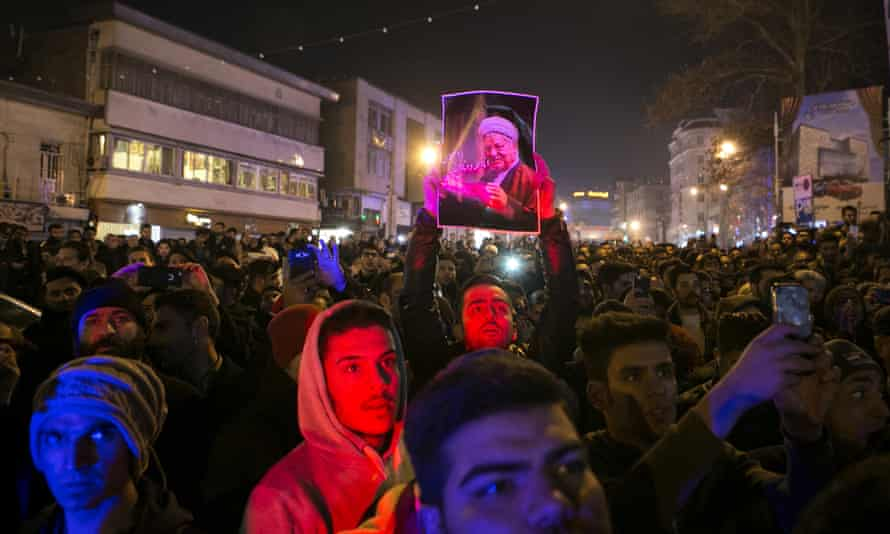 A mourner holds up a picture of Ali Akbar Hashemi Rafsanjani