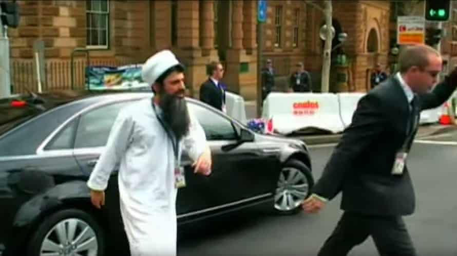 A man dressed as Osama Bin Laden and another man in a suit on the road