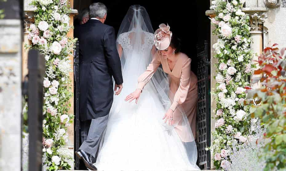Catherine, Duchess of Cambridge, arranges the train of her sister Pippa Middleton as she arrives with her father Michael Middleton for her wedding