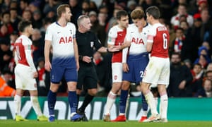Tottenham's Dele Alli rubs his head after being hit by a bottle at the Emirates on Wednesday.