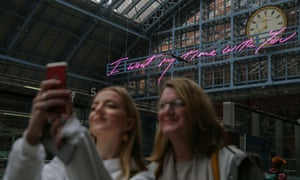 Visitors take a selfie in front of Tracey Emin's installation at St Pancras International station.