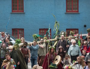 The May Day King and Queen lead the Greenmen of Glastonbury in carrying this year's maypole