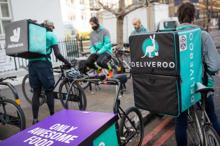 Deliveroo cycle couriers waiting for orders in London.