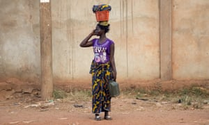 A woman stands by a road in the Central African capital, Bangui, using a mobile phone.