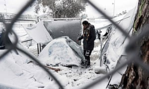 A man stands next to a snow-covered tent in the Moria camp on the island of Lesbos.