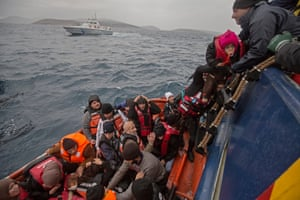 Refugees are helped from the liferaft on to the main Moas ship, with a Greek coastguard vessel in the background.