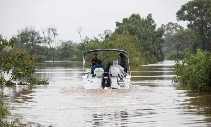Shaun Boland goes out on a friend's boat to inspect his property where he lived with his wife and two children in Pitt Town Bottoms.