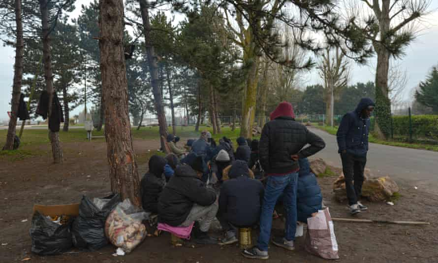 A group of Sudanese migrants near Ouistreham ferry terminal warming their hands over a fire.
