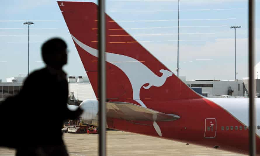 silhouette of a man in front of a qantas plane on the tarmac