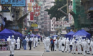 Government investigators wearing protective suits gather in the Yau Ma Tei area in Hong Kong today