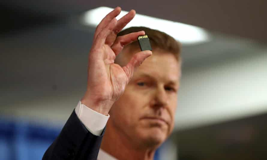 The US attorney David L Anderson holds an SD memory card as he speaks during a news conference on Monday in San Francisco.