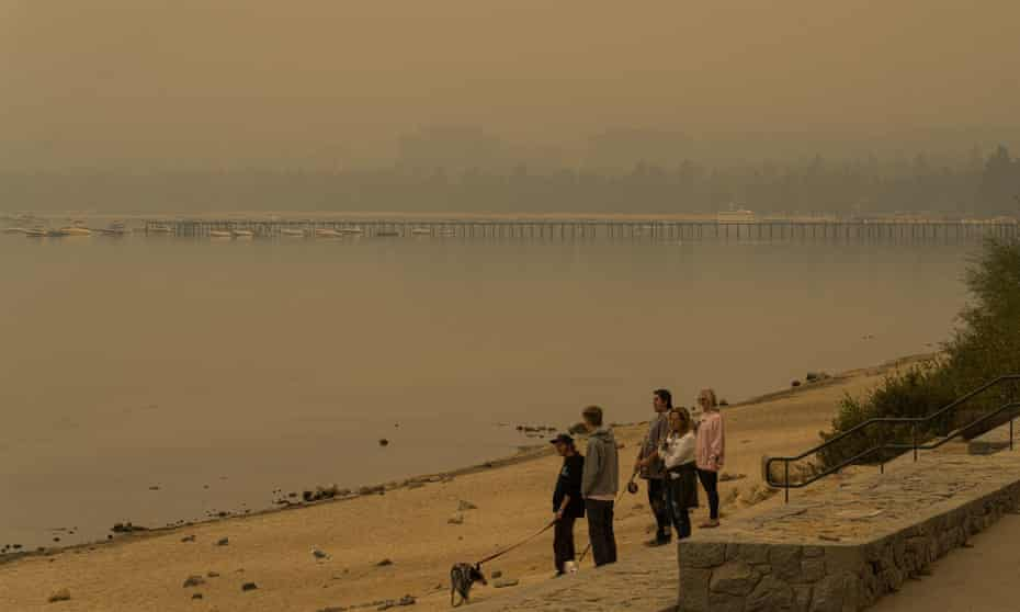 Visitors walk along El Dorado Beach, and wildfire smoke all but obscures the view of the lake and hotels at the South Lake Tahoe on Thursday.