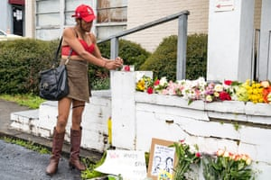 Mourners visit and leave flowers at the site of two shootings that occurred yesterday at spas across the street from one another.