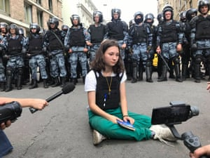 Moscow police stand by as Olga Misik , 17, blocks their path while holding a copy of the Russian constitution.