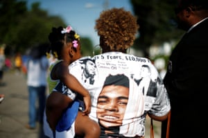 A spectator holds her child as the funeral procession takes p[lace