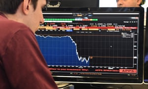 A journalist looks at a screen showing a plunging pound