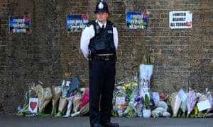 A police officer stands near tributes and flowers in Finsbury Park, London