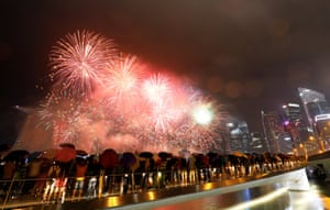 People shelter under umbrellas during Singapore's fireworks display.