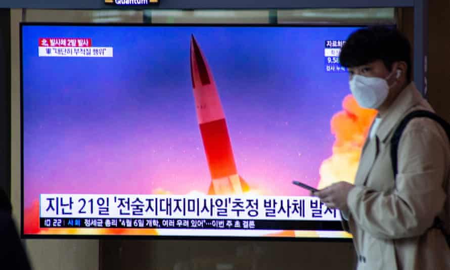 A man in Seoul walks past a TV screen airing a report on North Korea's latest missile launch