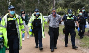 A man is detained during a planned anti-lockdown protest in Melbourne on Saturday.
