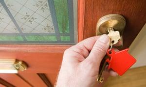 A person opens a door using a key