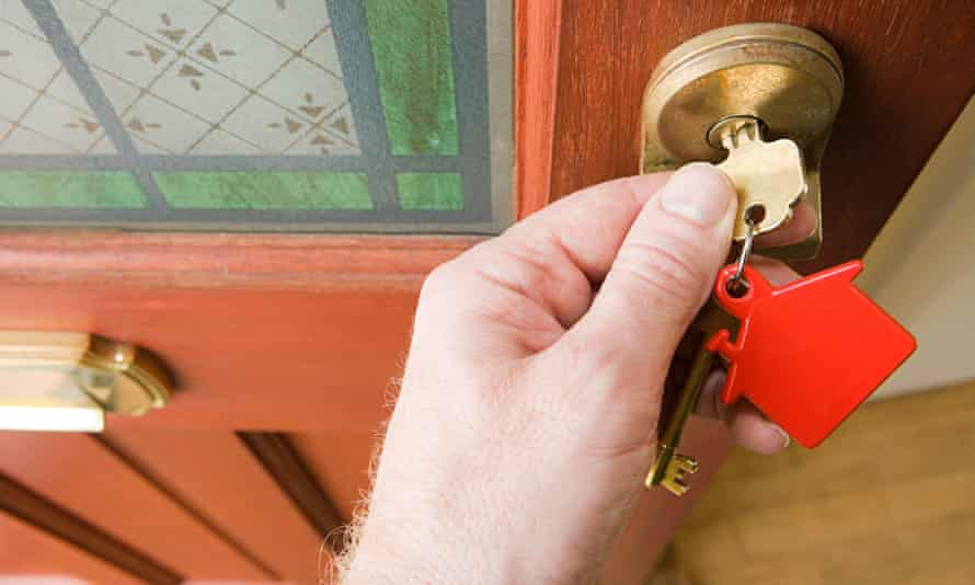 A hand opening a door with set of house keys