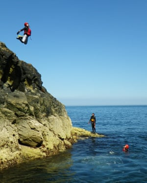 A person jumps from a cliff on a Celtic Quest Coasteering trip.