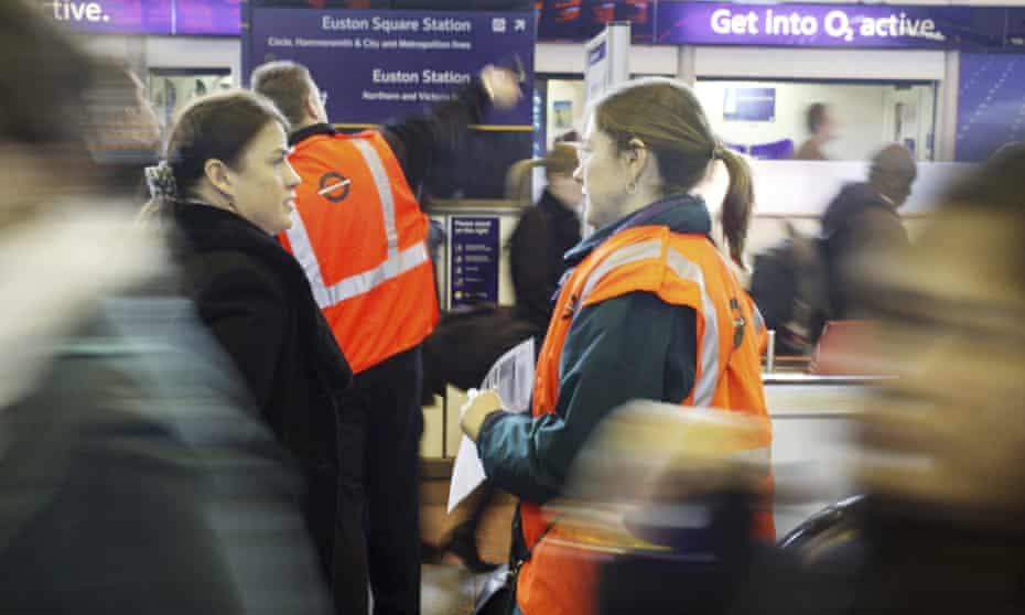 London Underground staff helping commuters.