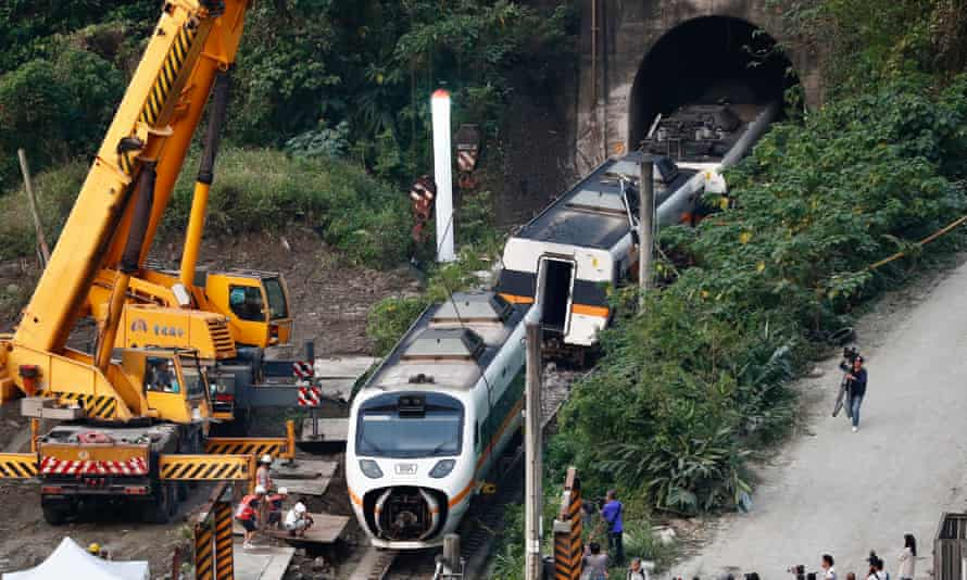 Rescuers remove parts of the train which derailed in a tunnel north of Hualien County, eastern Taiwan.