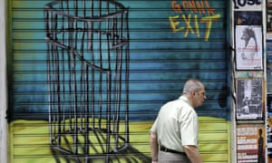 A Greek man passes graffiti in Athens as the perhaps ultimate meeting on the Greece debt crisis convenes.