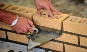 An apprentice lays bricks