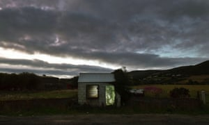 A former customs guard hut is illuminated on the Irish border in Ravensdale, Ireland.